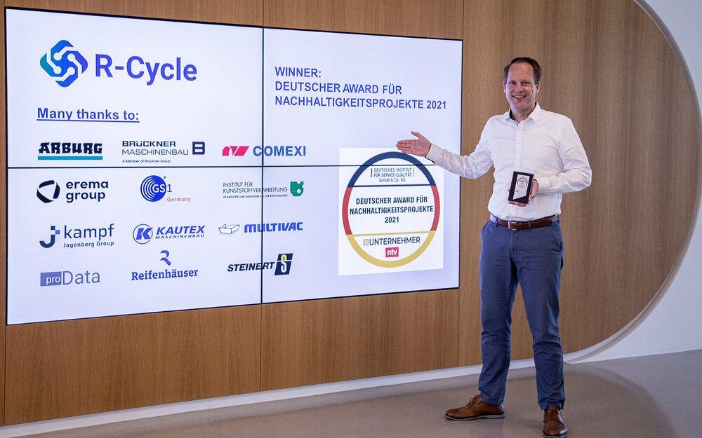 Dr. Benedikt Brenken, Director of the R-Cycle Initiative, accepts the award on behalf of the consortium.